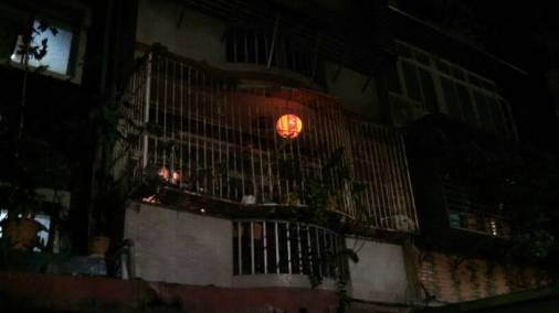 Another lantern hangs from an apartment across the street. The lanterns are guides for the spirits of dead relatives so they can find their homes after wandering about.