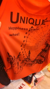 "The shirt reads, ""UNIQUE... Hepplness ferris whee!"" It's unique, alright..."